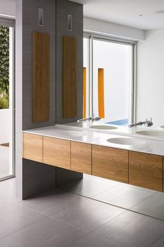 mirrored wall, wall mounted faucets, wall mounted wood vanity with corian counter and integrated sinks