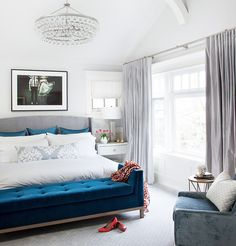 Light-tone bedroom with white bedding, crystal chandelier, and blue tufted bench.