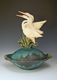 Ship Date: 2-4 weeks One of a kind Ceramic Herons sculpted with reeds and attached to lid of wheel thrown bowl. Bright white glaze on birds, with matte air brushed underglazed bowl. Carved lid incised