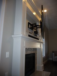 Custom mantle/TV cabinet w/carrera marble surround and granite hearth. TV is on fully articulating/telescoping mount to allow easy access to storage/components behind