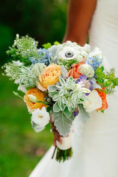 Colorful rustic bouquet featured coral and apricot roses, purple pincushions, blue delphinium, anemones, Queen Anne's lace, dusty miller, brunia berries, and pittosporum. Just gorgeous! |   Photo by Lyn Ismael: Evocative Imagery of Love Stories