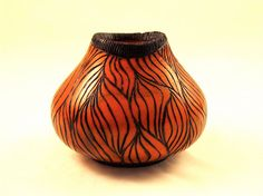 Woodturning: Natural Edge Hollow Form, pyrography motif, stained orange and sealed with lacquer. $100,00, via Etsy.
