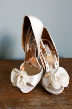 Contemporary white wedding heels with delicate looking flowers attached to the strap over the peep-toe. Superlative summer wedding shoes!