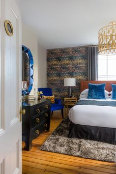 A feather-like look on the accent wallpaper draws the eye to the back of the room. A brown leather headboard and white bed linens are decorated by a pair of velvet blue throw pillows. A deeper royal blue armchair and 3D geometric mirror continue the accent color. A shag rug brings a soft texture against the hardwood flooring and black dresser.