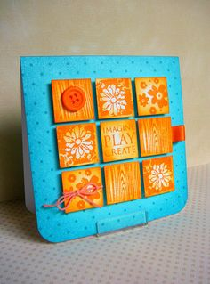 stunning handmade card ... turquoise base with orange & yellow inchies in a nine square pattern ... cute designs on the inchies ...