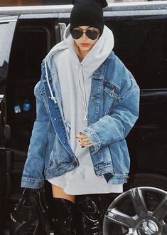 Pinterest: DEBORAHPRAHA ♥ Hailey Baldwin in New york city walking around wearing oversized denim jacket and grey hoodie paired with ray ban sunglasses, beanie and over the knee boots. I love her style!