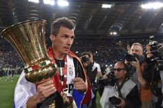 Juventus' forward from Croatia Mario Mandzukic celebrates with the trophy after winning the Italian Tim Cup final football match AC Milan vs Juventus on May 21, 2016 at the Olympic Stadium in Rome.  Juventus won 0-1 in the extra time.     AFP PHOTO / TIZIANA FABI / AFP / TIZIANA FABI