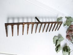 This rusty rake head bends at a 90 degree angle from the handle and the tines. It is beautifully and evenly rusted across its entire surface. It could be attached to an old board and make a really neat repurposed wine glass rack or simply a found item as part of a vintage, rustic, or country themed decor.  14 1/2 wide