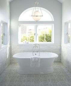 Stunning bathroom features vaulted ceiling accented with sphere chandelier over freestanding bathtub paired with wall-mounted tub filler surrounded by windows on pale blue walls paired with white marble backsplash over mosaic marble floor.