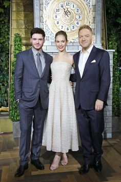 In Nicholas Oakwell Couture with Richard Madden and Director Kenneth Branaghat at the Cinderella Moscow premiere.   - ELLE.com