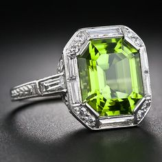 A gorgeous and glistening, bright lime green octagonal emerald-cut peridot with accentuated cut corners is framed in platinum with sleek baguette diamonds punctuated on each corner with a pair of twinkling single-cut diamonds. The under gallery is ornamented all around with graceful open scroll work and the ring shank shimmers with a pair of straight baguette diamonds leading to decorative hand engraving. A stunning and sophisticated Art Deco delight - circa 1930