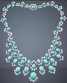 A turquoise and diamond necklace, by Bulgari, 1960s.   Of fringe design, the front of the necklace composed of twelve pendants, each set with oval turquoise cabochons, accentuated by brilliant-cut diamond partial surrounds, suspended from a similarly-set undulating neckchain, signed Bulgari, inner circumference 35.0cm. Bonhams.