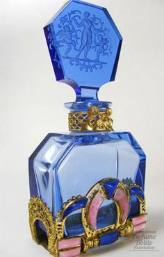 CZECHOSLOVAKIAN » #BLUE JEWELED BOTTLE, 1930-38. The intense #blue color of this bottle may be seen in items from this glass house. It is striking when combined with opaque pink and blue curved glass stones set in the Egyptian influenced metal filigree. The intaglio molded classical figure of woman with cupids is similar to Hoffman stoppers but lacks the impressed butterfly.