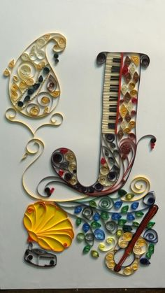 Quilling for monogram J fused with musical instruments and a peacock