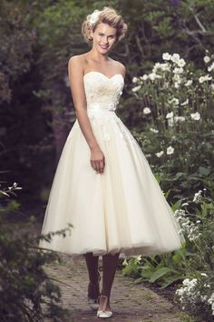 This vintage inspired wedding dress accenting with subtle lace on the strapless sweetheart neckline bodice topped by tea length simple ball gown tulle skirt.
