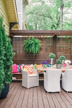 Chic deck boasts a long built in bench lined with colorful outdoor pillows fitted with wood lattice privacy fence facing a light wood outdoor dining table lined with a mix of white wicker dining chairs as well as white slipcovered dining chairs.