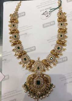 Stunning gold necklace studded with diamonds and emeralds. Gold necklace with dancing peacock motifs and pendant. Necklace with guttapusalu hangings. Indian Gold Jewellery Design, Gold Chain Design, Antique Jewellery Designs, Bridal Jewellery, Handmade Jewellery, Indian Jewelry, Gold Mangalsutra Designs, Gold Earrings Designs, Necklace Designs