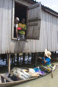 Africa |   A woman sells fried fish on her baot in Makoko slums in Yaba, Lagos, Nigeria,
