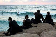 Surfing Israel - Ebrei ultra-ortodossi guardano i surfisti durante la festa di Sukkot, dalla spiaggia di Ashdod (Ap/Balilty)