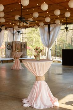 High-top #cocktail tables covered in blush satin linens. So country chic with the string lights and paper lanterns! {@jamieblow}