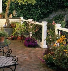 A brick-paved porch becomes one with the backyard beyond, thanks to careful plant selection. Standard roses and pots of bright annuals echo the tones of the plantings in the rest of the yard.