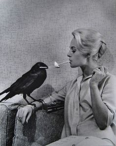 Tippi Hedren having her cigarette lit by a crow on the set of The Birds
