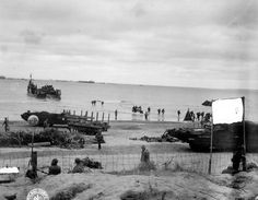 """Normandy landings: The censor has painted over the sign reading """"RED BEACH HQ"""" as US troops continue to land in June 1944. Amphibious craft are operating on the beach bringing in materiel and supplies."""