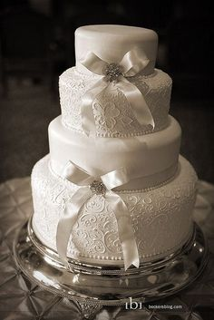 Classic lace and sweet silky white bows on this wedding cake are a hit!