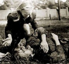 A 10-year-old Polish girl cries over the body of her older sister.  Starving, they had been digging for potatoes in a field in Warsaw when the Luftwaffe turned their machine guns on them.