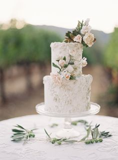 Delicate textured cake with blush blooms via Laurie Arons