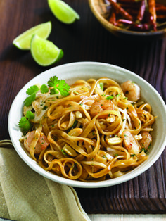 Pad Thai - 1/2 lb Asian-style rice noodles, 1/2 cup Kikkoman Thai Peanut Sauce, 1/4 cup soy sauce, 1 T lime juice, 2 T sugar, 3 T sesame oil, 1/2 lb boneless, skinless chicken breast, 3 cloves garlic, 1/3 pound bean sprouts, 4 scallions, 1/2 lb cooked baby shrimp, 2 T cilantro, 1/4 cup peanuts, lime wedges