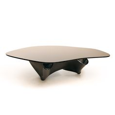 A monumental and rare black glass coffee table with handkerchief shape base and irregular glass top. Imported from USA to London for an estate in Hyde Park. This piece was produced prior to 1992 when Laurel owned Lumen Essence, Inc (L.E.I.) and she used very little black glass. At the time, she went by the name Laurel Clark. Signed L.E.I #13 on the base and authenticated by the late designer's employees at Fox Fire Glass LLC. WEAR: Wear consistent with age and use. Three small chips on th...