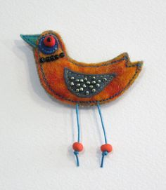 Felt, glass beads, handmade plastic bead and machine embroidery. It measures about 8/7 cm with the legs and has a metal pin attached to the back. Please note that color may vary due to the monitor settings. Thank you for visiting my shop.