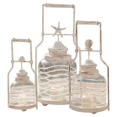 Metal candleholders showcase seaside-inspired finials and textured glass cloches.