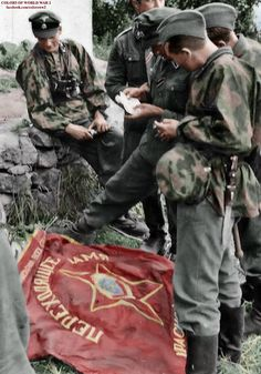 Men of Leibstandarte Division proudly displaying for the photographer the captured standards of Soviet units they have beaten in 1941.