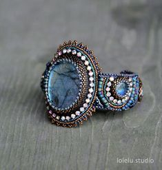 The listing is for this beautiful bead embroidered bracelet.  The focal point is a great quality colorful blue flashing labradorite cabochon.  The bracelet was bead embroidered by hand with size 15 and 11 seed beads, delica beads, natural freshwater pearls and Swarovski stones.  The bracelet