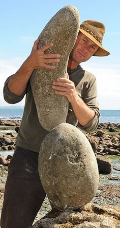 Hard at work: Adrian Gray feels for the balancing point of rocks so he can create the sculptures