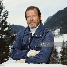 English actor Roger Moore poses on a snowy mountain, circa 1990.