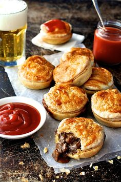 Party Pies (Aussie Mini Beef Pies) with Olive Oil, Chuck Steaks, Onions, Garlic Cloves, Tomato Paste, Beef Stock, Red Wine, Bay Leaves, Salt, Black Pepper, Corn Starch, Water, Egg Yolks, Shortcrust Pastry, Frozen Puff Pastry Sheets, Tomato Ketchup.