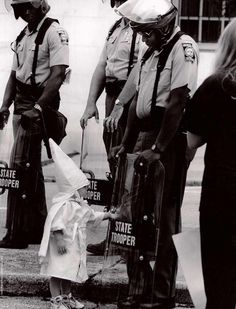 Here is a Georgia State Trooper in riot gear at a KKK protest in a north Georgia city back in the 80s. The Trooper is black. Standing in front of him and touching his shield is a curious little boy dressed in a Klan hood and robe.