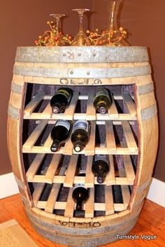 cut a square out of a wooden barrel and place racks in the inside and you have a creative wine rack holder