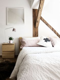 Bedroom with linen bedding, wood beams.