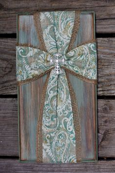 Handmade, ready to hang, rustic cross. A stained, painted, and distressed piece of select pine with beveled edges and a cross made of secured natural burlap and a green and ivory paisley burlap, along with a crystal cross embellishment in the center. Approximately 9 wide, 16 long, and 1 deep. If you would like this cross on solid stained wood instead of the colored distressed, contact me before ordering or attach a note at the time of purchase. These make wonderful gifts for any occasion,...