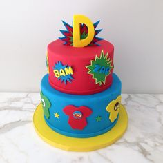 Superhero baby shower cake: onesie, hero, red, blue, yellow, green, batman, superman, baby, green lantern, marvel