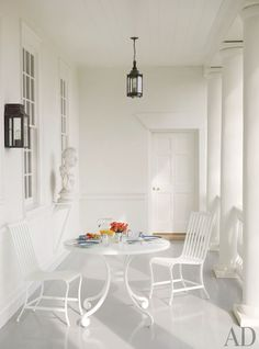 An all-white front porch is accented by a black lantern and sconce.