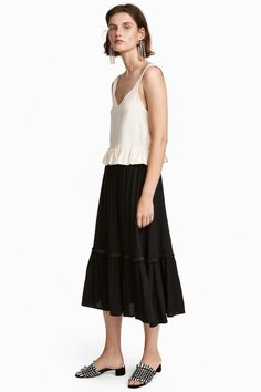 Wide, calf-length skirt in soft fabric with a frill-trimmed, elasticated waist and a seam at the hem with a short fringe trim and wide flounce.