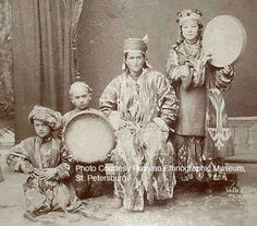A troupe of musicians featuring two women and two young boys. Note the ikat coats worn by the woemn as well as the dress of the young boys. These people are probably Uzbeks.