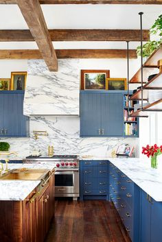 A stunning kitchen with marble backsplash, blue cabinents, and wooden accents