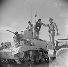 An officer of the Royal Tank Regiment gives orders from his Daimler scout car to the commander of a Stuart tank in the Western Desert, 18 Ju...