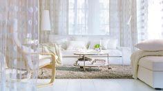 """Ein helles Wohnzimmer mit KIVIK 3er-Bettsofa mit Bezug """"Blekinge"""" weiß mit vielen Textilien u. a. OFELIA BLAD Kissen + OFELIA Plaid weiß, um..."""